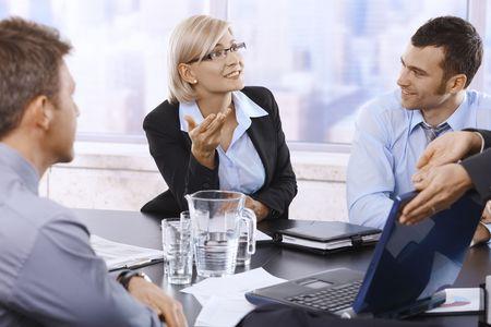 profesionistas: Profesionales de hablar en la reuni�n discutiendo trabajan, mirando port�til ensaya un juego brillantes.