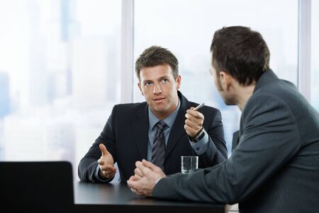 Two businessmen discussing tasks sitting at office table. photo