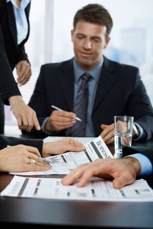 Businesspeople reviewing business report. Focus on hand in middle. Stock Photo - 6578481