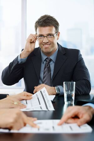 trait: trait of successful businessman smiling at camera hand up at glasses at meeting. Stock Photo