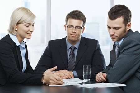 Mid-adult professionals at businessmeeting, looking at documents deep in discussion. Stock Photo - 6578816