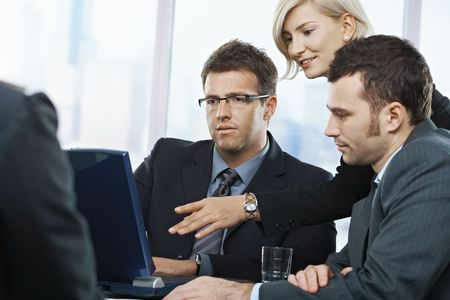 co work: Business people looking at laptop, talking at meeting table in office,