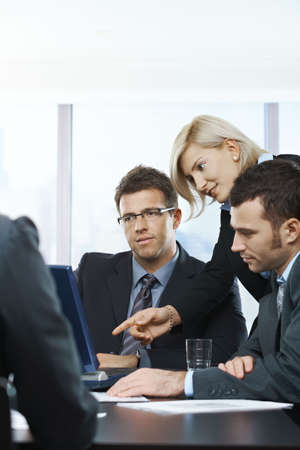 Business people looking at laptop, talking at meeting table in office, photo