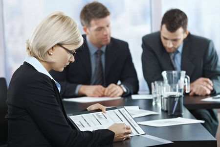 Professional businesswoman checking documents at business meeting with coworkers in background. photo