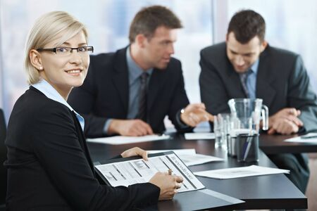Smiling businesswoman holding documents sitting in meeting room with coworkers. Stock Photo - 6578743