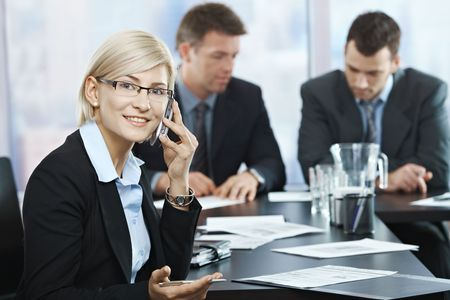 conference call: Successful businesswoman smiling talking on phone at meeting with businessmen in background.