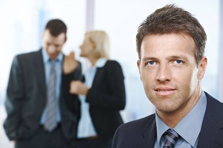 Confident businessman in focus, with standing colleagues talking in the background. photo