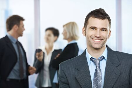 looking good: Portrait of happy businessman with coworkers talking in the background.