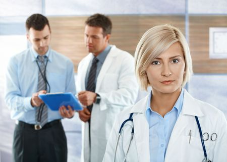 Healthcare workers on hospital corridor female doctor in front looking at camera. photo