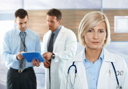 consultant physicians: Medical team on hospital corridor female doctor in front looking at camera, smiling.