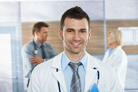 serious doctor: Medical team on hospital corridor mid-adult doctor in front looking at camera, smiling.