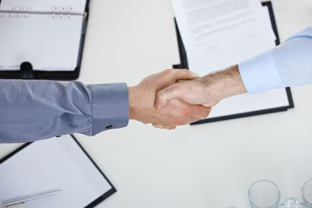 Closeup of hands, businessmen shaking hand over meeting table in office. Stock Photo - 6578328
