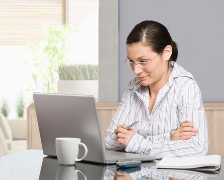 mujeres pensando: Joven sentado en el escritorio, trabaja con el equipo port�til en casa, sonriendo.