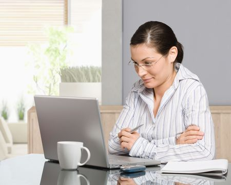 Young woman sitting at desk working with laptop computer at home, smiling. Stock Photo - 6579010