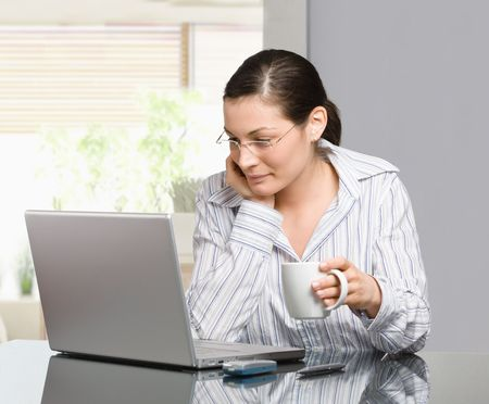 Young woman sitting at desk working with laptop computer at home, smiling. photo