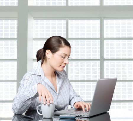 Young businesswoman is thinking over  her laptop. photo