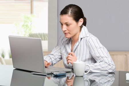 Young woman sitting at desk working with laptop computer at home, serious, thinking. photo
