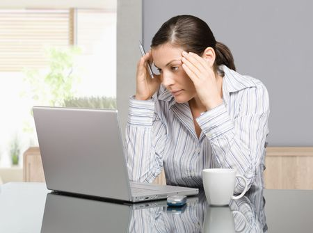 Young woman sitting at desk working with laptop computer at home, seus, thinking. Stock Photo - 6579007