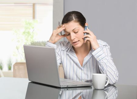 Young woman sitting at desk working with laptop computer at home, talking on mobile phone. photo