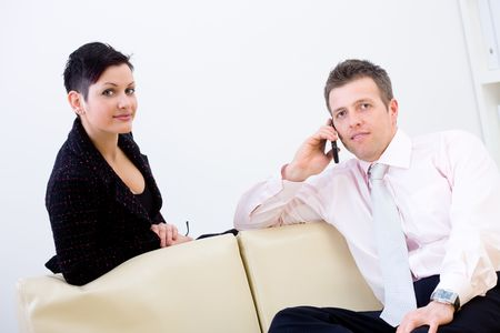 Young businesspeople working together, sitting at couch in office. Man talking on mobile phone. photo