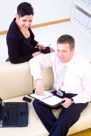 high angle shot: Happy businesspeople sitting at couch, working together, smiling. High angle shot. Stock Photo
