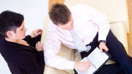 high angle shot: Casual businesspeople working together, sitting on couch. They are checking notes in personal organizer. High angle shot. Stock Photo