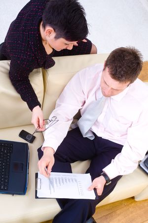 Young businesspeople working together, sitting at couch in office. Overhead shot. photo