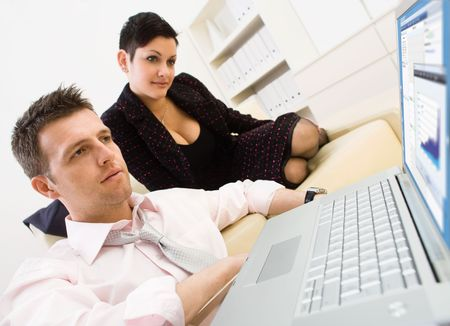 Businessman sitting on floor and teamworking on laptop computer with businesswoman. They look workoholic.  photo