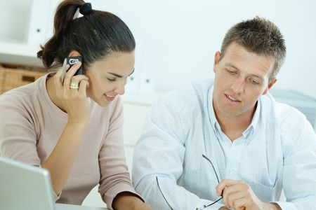 calling businessman: Couple working on laptop computer at home office, happy, smiling. Woman calling on mobile phone. Stock Photo