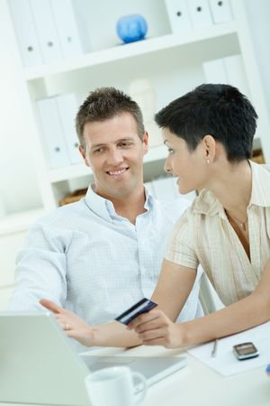 Happy young couple purchasing online with credit card  from home. photo
