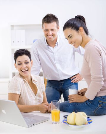 white collar worker: Happy, smiling office workers sitting at desk, looking at laptop computer screen.