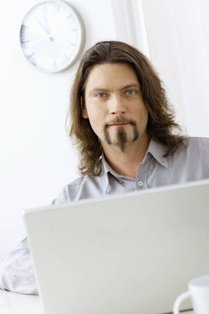 Portrait of casual businessman working at desk using laptop computer, looking at camera. photo