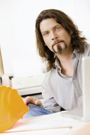 Portrait of architect working in office, looking at camera. photo
