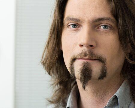hombre con barba: Retrato de detalle de hombre de aspecto grave con pelo largo y barba.