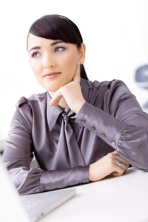 Joven empresaria pensando sobre su portátil, apoyándose en su mano, sonriendo. Foto de archivo - 6592994