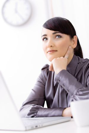Young businesswoman thinking over her laptop, leaning on her hand, smiling. photo
