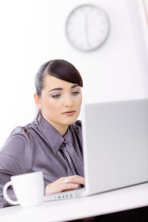 Businesswoman using laptop computer in brightly lit office, looking at screen. photo