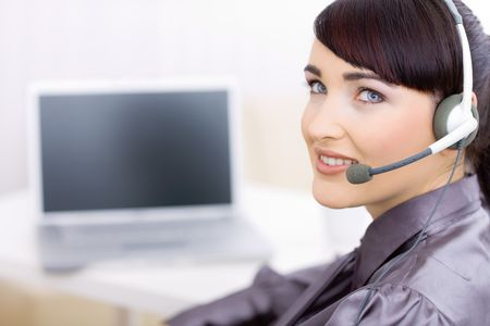 Happy young female customer service operator talking on headset, sitting in front of computer screen, smiling. Stock Photo - 6592968