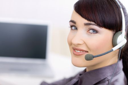 Happy young female customer service operator talking on headset, sitting in front of computer screen, smiling. Stock Photo - 6592962