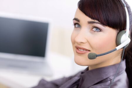 administrativo: Happy young female customer service operator talking on headset, sitting in front of computer screen, smiling.