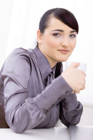 Young businesswoman drinking coffee, sitting at office desk, smiling. photo