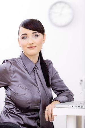 Young businesswoman sitting at office desk, using laptop computer, looking at camera, smiling. photo