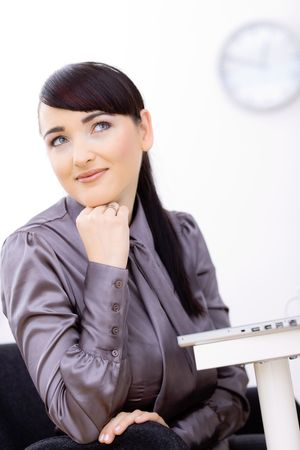 Young businesswoman sitting at her office desk, leaning on her hand, daydreaming. photo