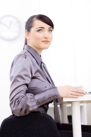 Young businesswoman sitting at her office desk, smiling and looking at up. Stock Photo - 6592985