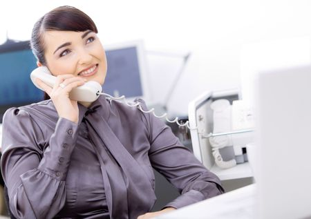 Happy young female customer service operator talking on landline phone, sitting in front of computer screens, smiling. photo