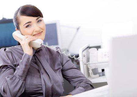 Young female customer service operator talking on landline phone, sitting in front of computer screens, smiling. photo