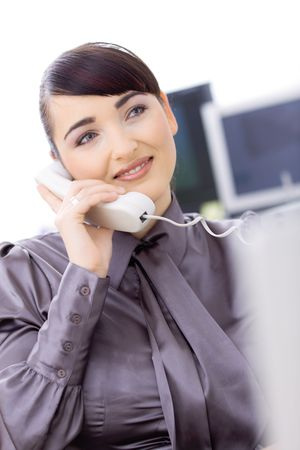 Happy young female customer service operator talking on landline phone, sitting in front of computer screens, smiling. Stock Photo - 6593015