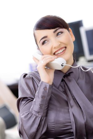 Happy young female customer service operator talking on landline phone, sitting in front of computer screens, smiling. Stock Photo - 6592981
