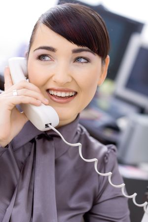 Happy young female customer service operator talking on landline phone, sitting in front of computer screens, smiling. Stock Photo - 6592975