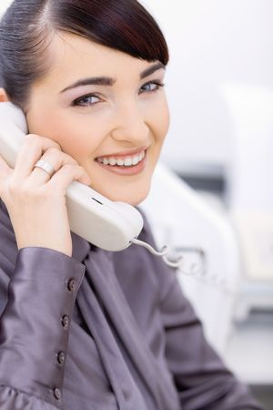 Happy young businesswoman talking on landline phone in office, smiling. photo